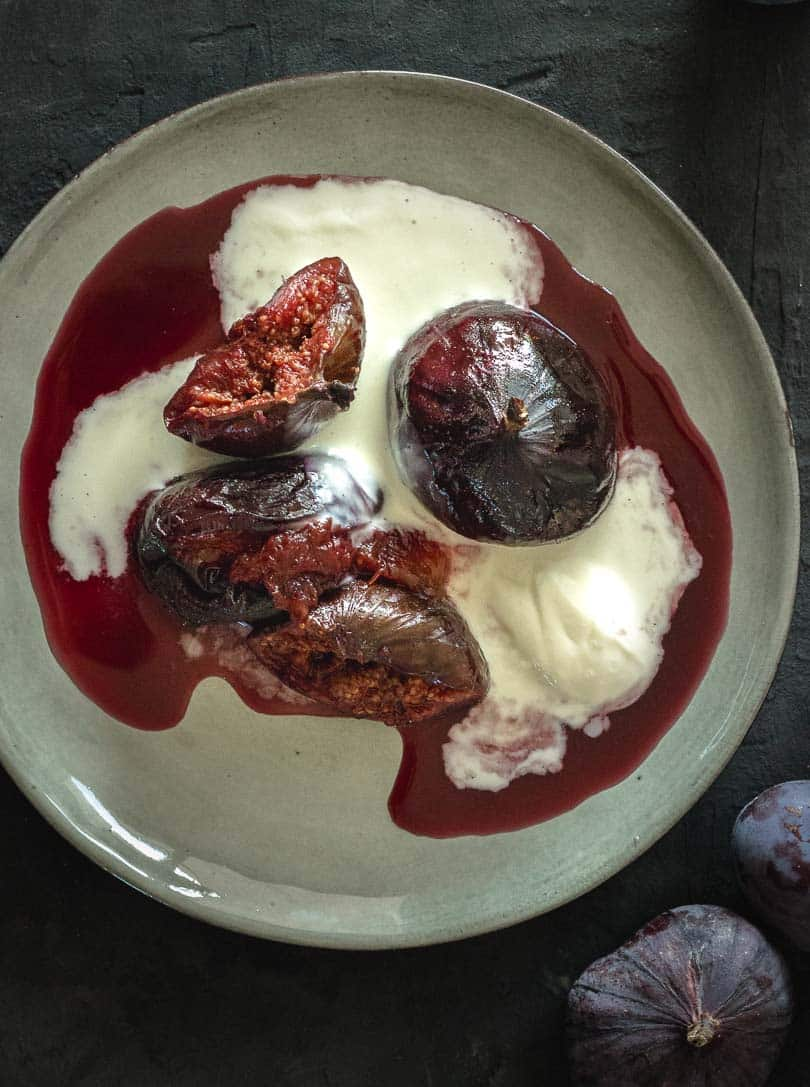Roasted figs in red wine with mascarpone cream on plate