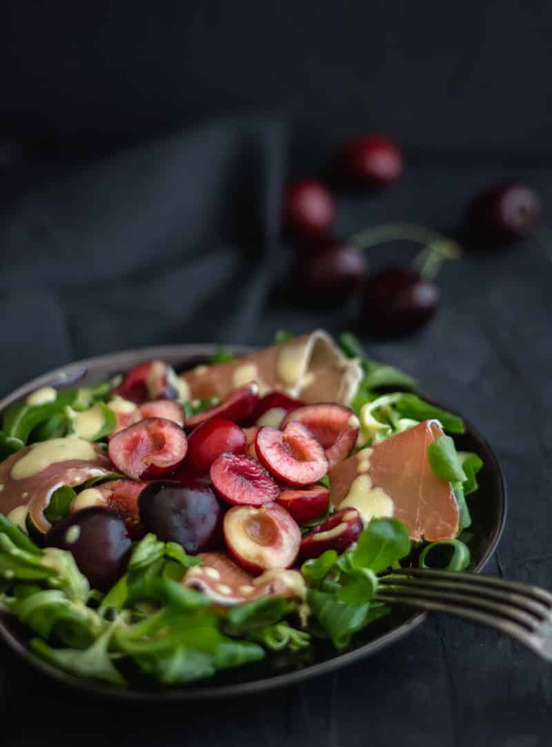 Summer salad with cherries and serrano on plate