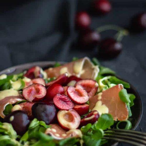 Salat mit Kirschen und Serrano auf Teller, Rezept