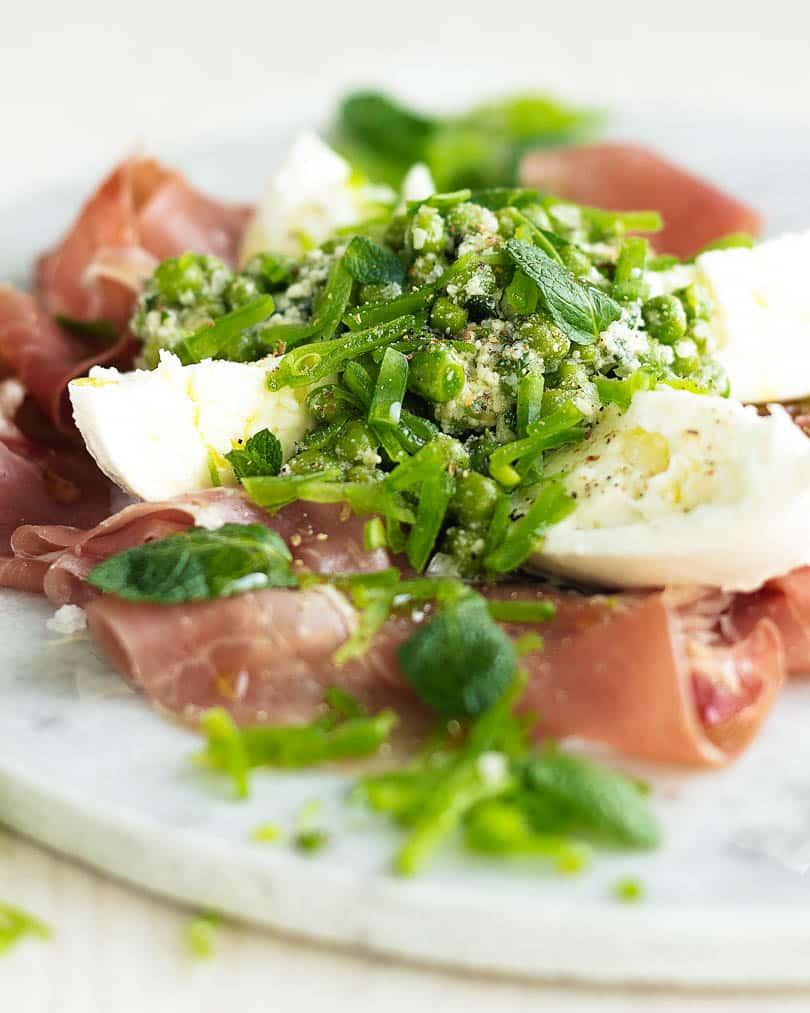 Mozzarella with prosciutto and peas on white plate
