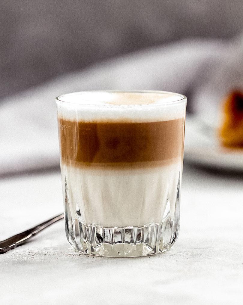 Karamellisierter Apfelkuchen mit Milchkaffee im Vordergrund