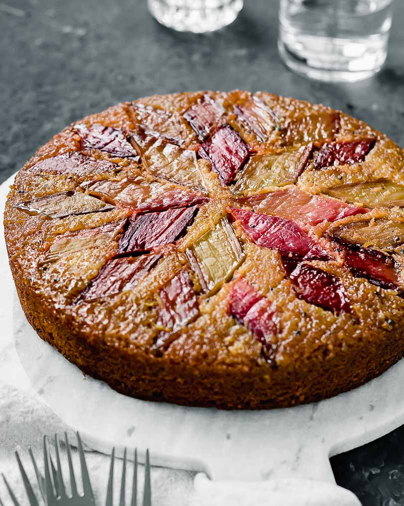 Rhubarb cake with orange and cardamom on white plate