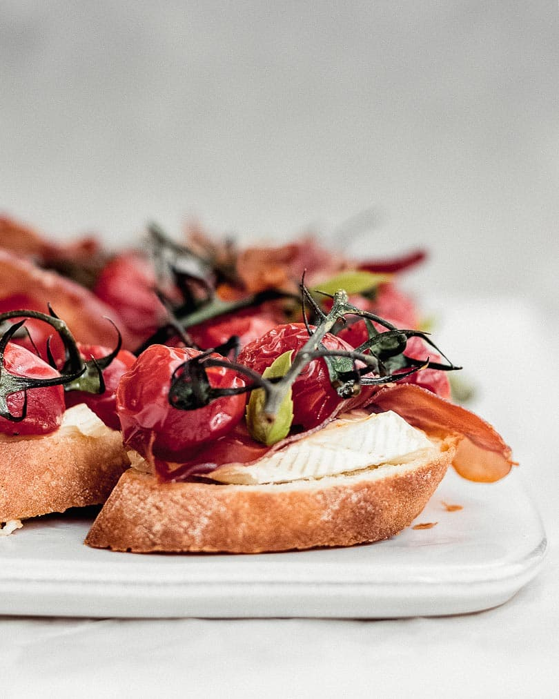 Brie crostini with caramelized tomatoes and serrano on white plate