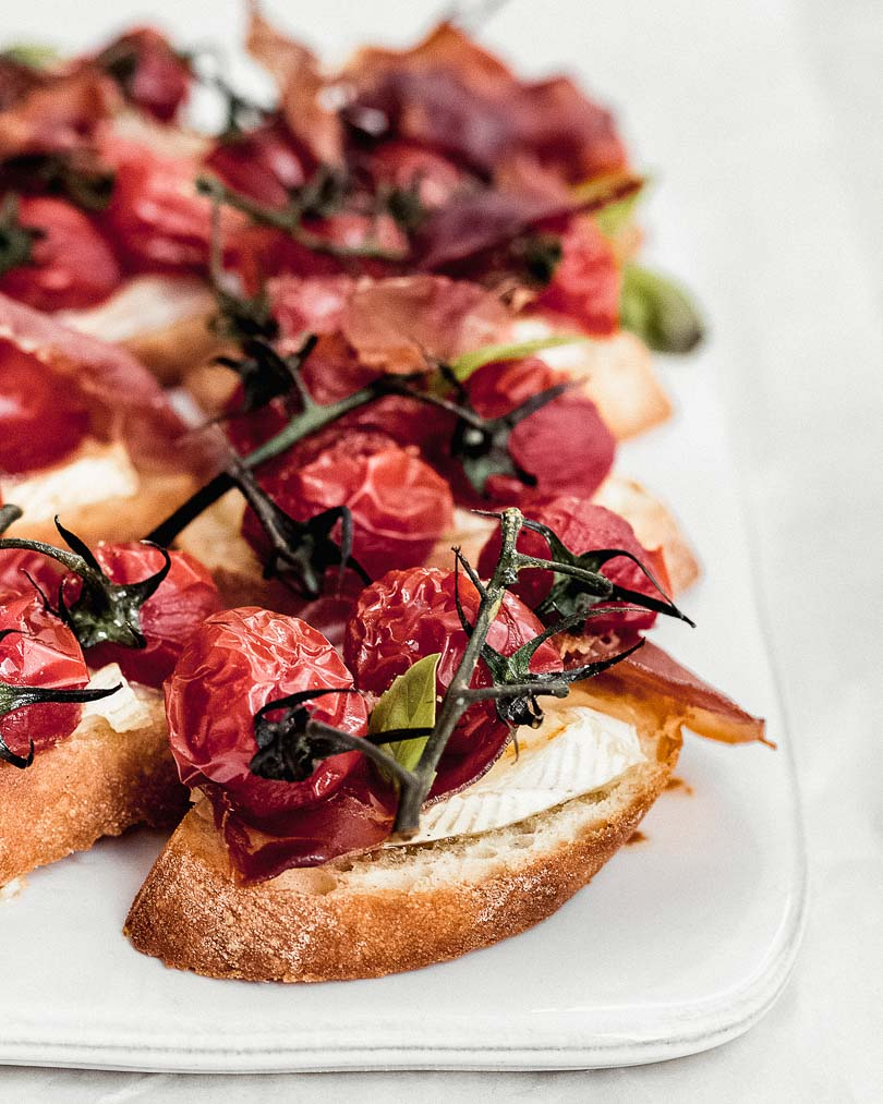 Brie crostini with caramelized tomatoes and serrano on white plate 45 angle