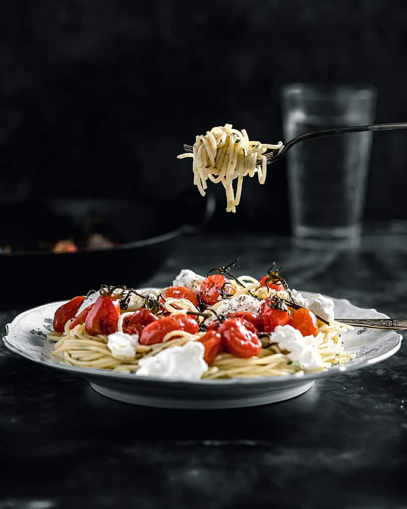 Spaghetti with caramelized tomatoes and burratta on a fork